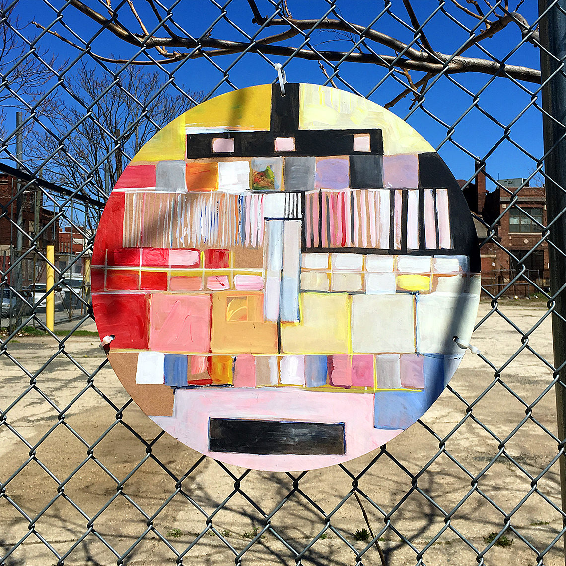 circlular painting hung on fence
