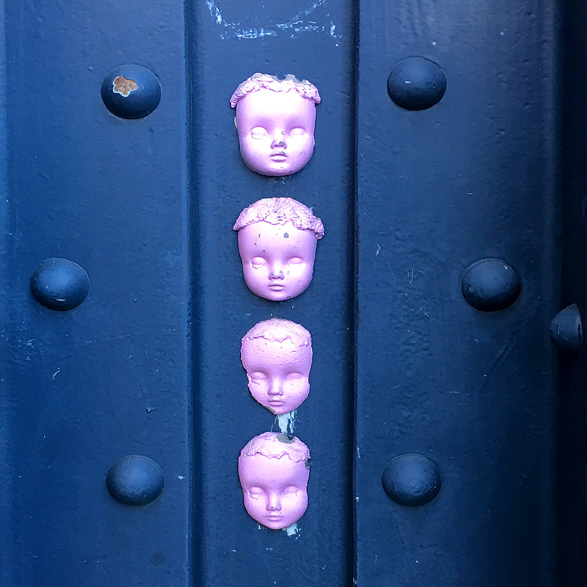 casts of doll faces stuck to a steel train support girder