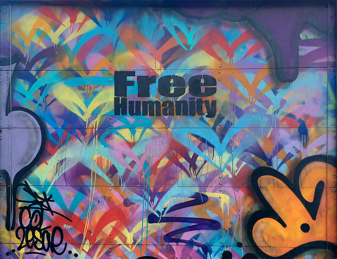 "colorful spray paint graffiti saying ""free humanity"""