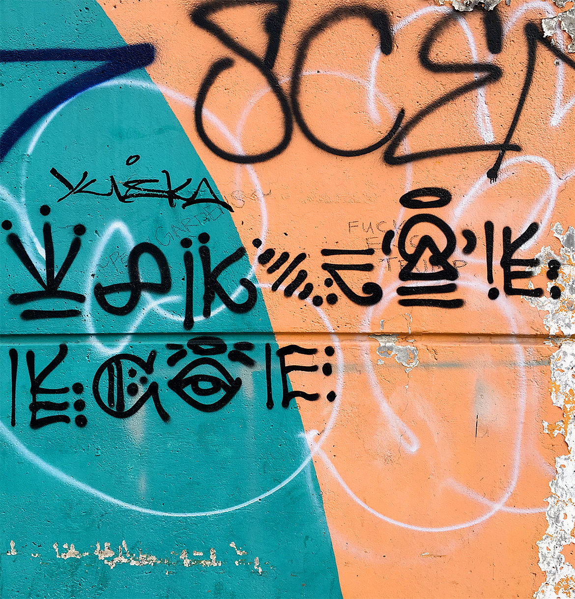 teal and orange wall with spray pain hieroglyphics