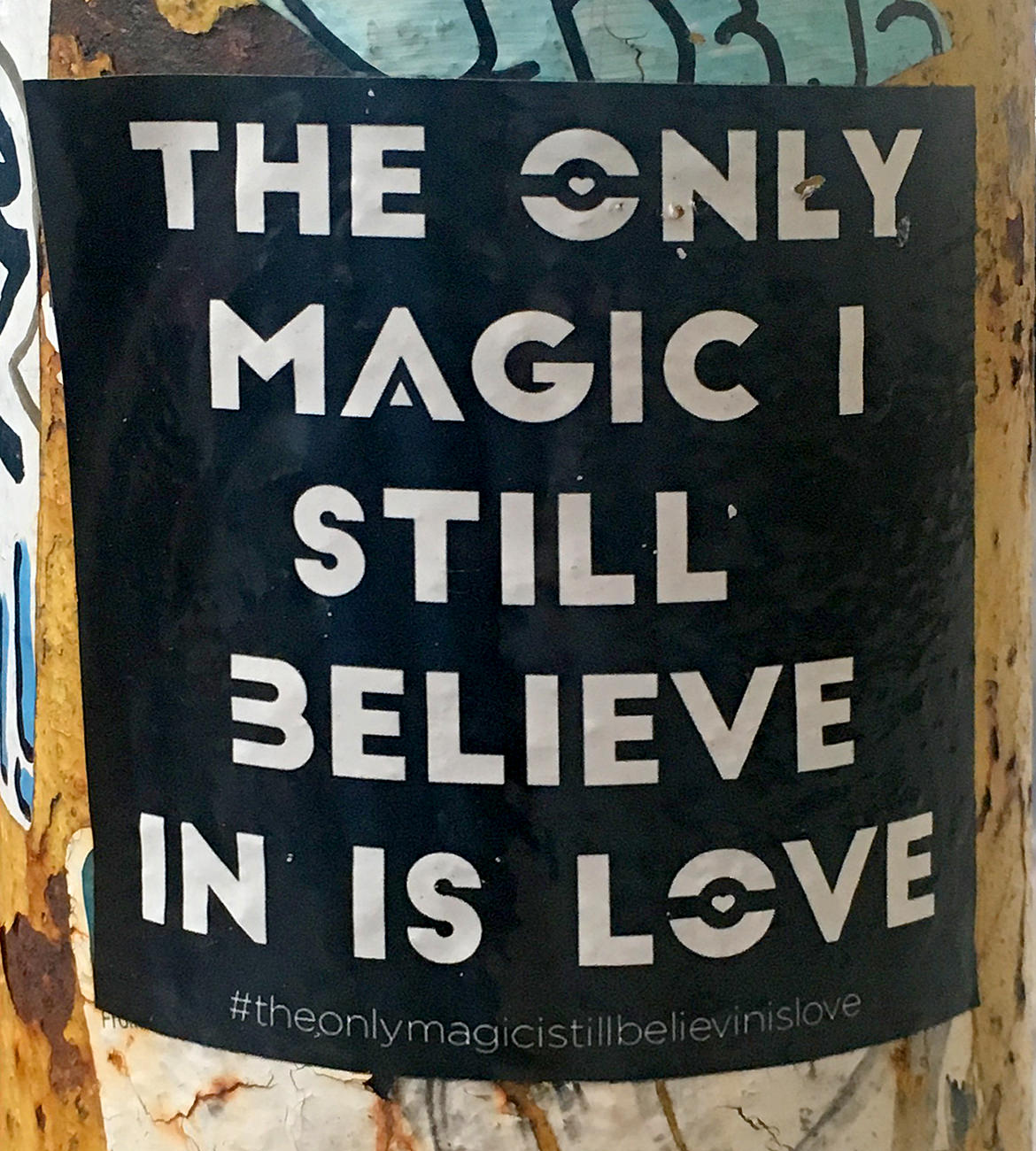 "black sticker with white text saying, ""the only magic I still believe in is love"""