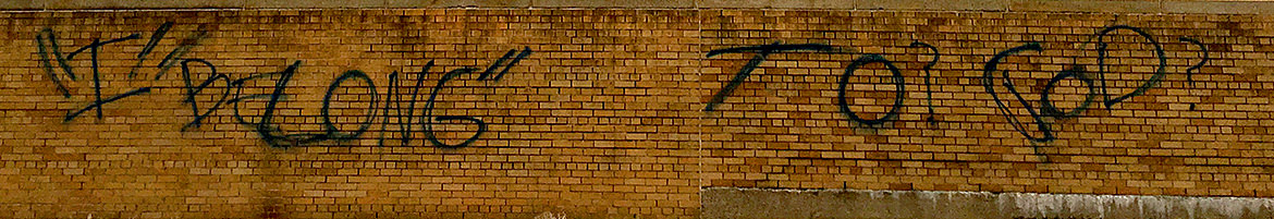 "Large spray painted lettering on a brick wall saying ""I belong to God"" with incorrect punctuation"