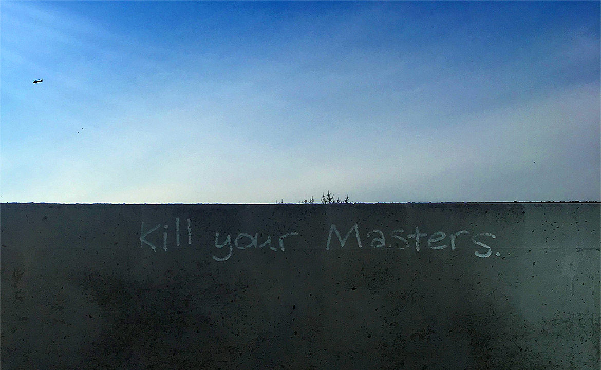 "Graffiti lettering saying, ""kill your masters"" on a wall with blue sky behind"