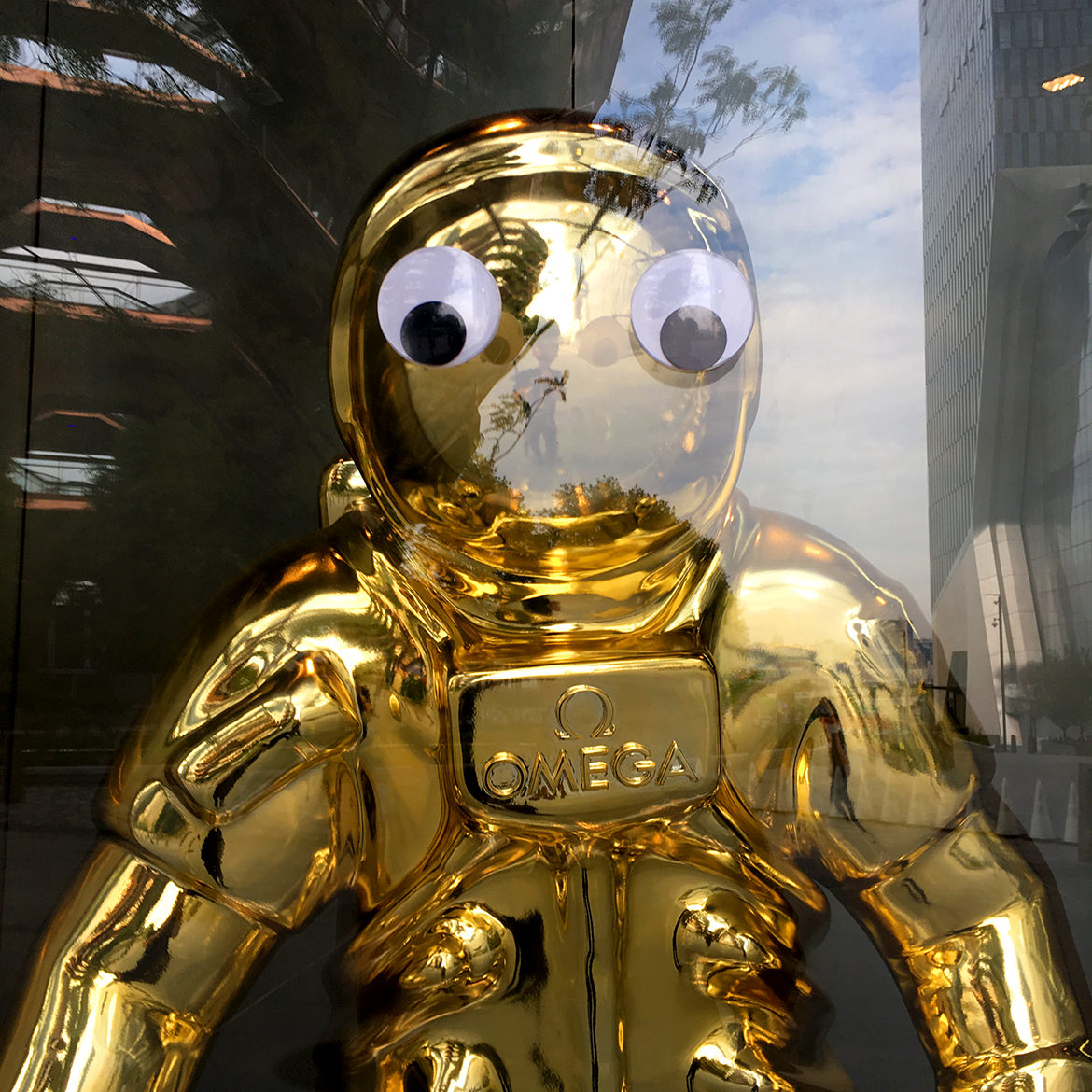 Large googly eyes attached to a store window overlaping a gold astronaut statue