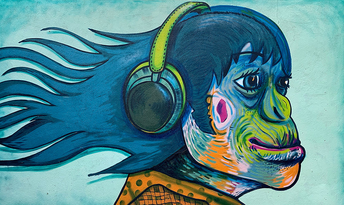 A mural painting of an female ape wearing headphones and smiling