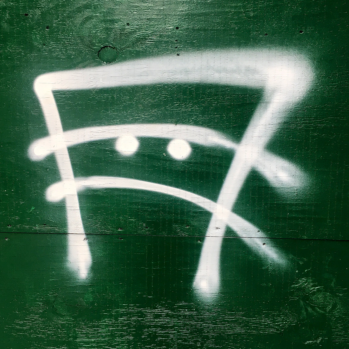 Spraypaint graffiti of a frowning face
