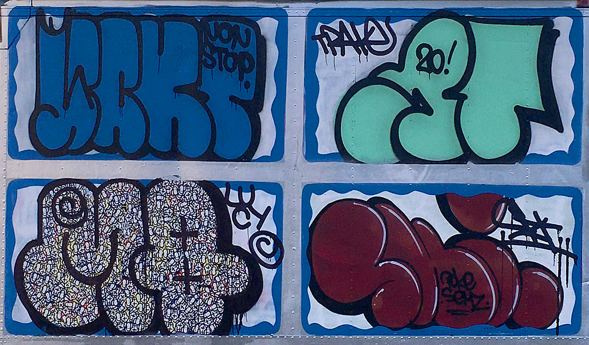 Four pack of spray paint graffiti lettering pieces on the side of a truck