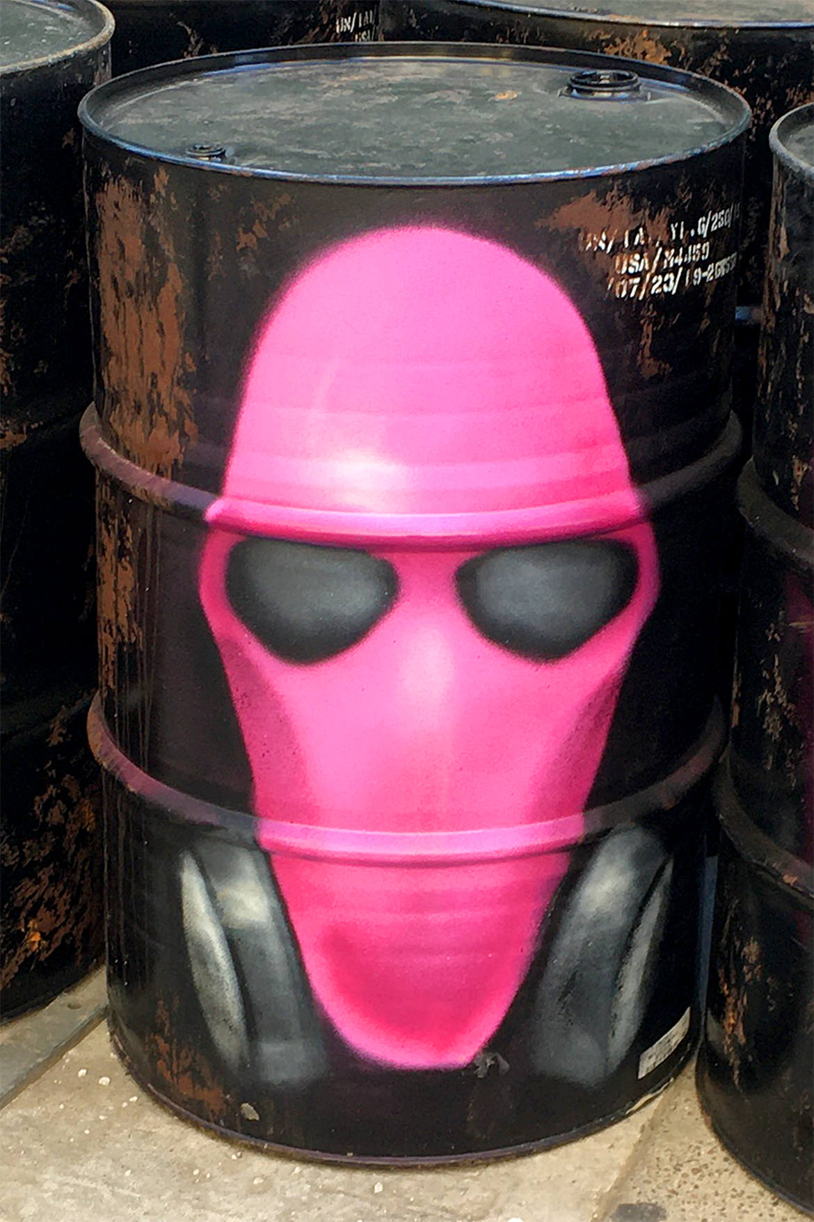 Spray paint graffiti art of a hot pink gas mask on an oil can