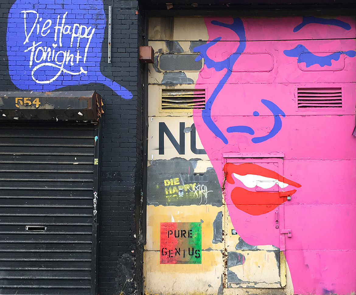 "Mural of a woman's face with a speech bubble saying ""Die happy tonight"""