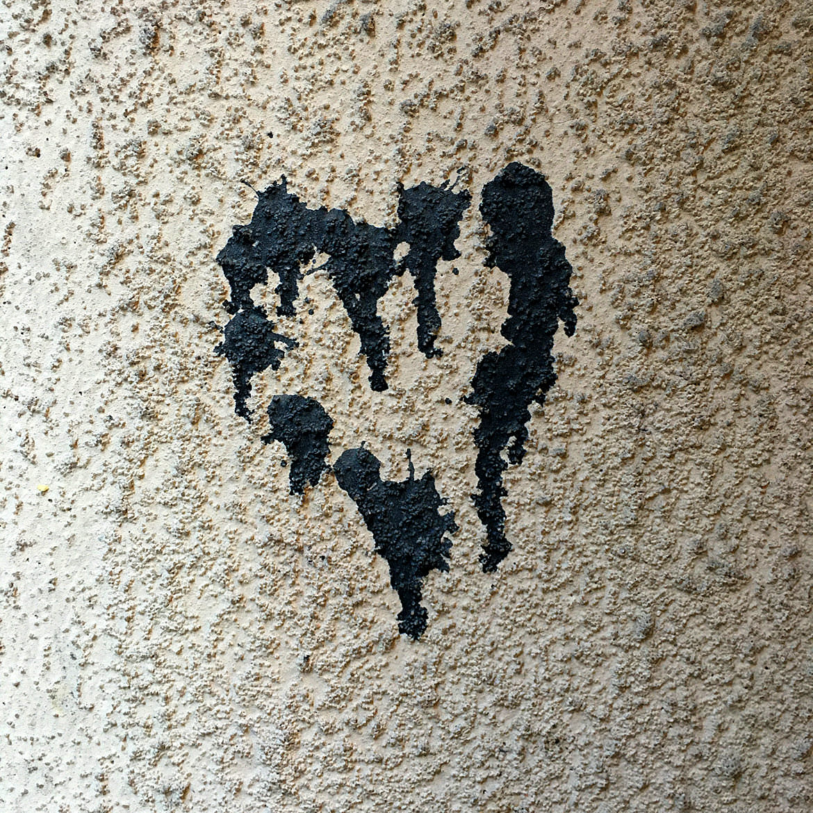 A black heart shape made of industrial glue remains on a stucco wall