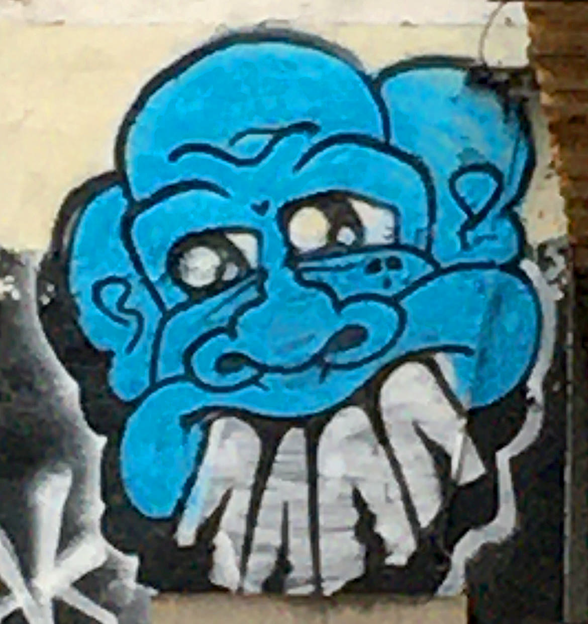 Spray paint graffiti blue cartoon face with large white buck teeth