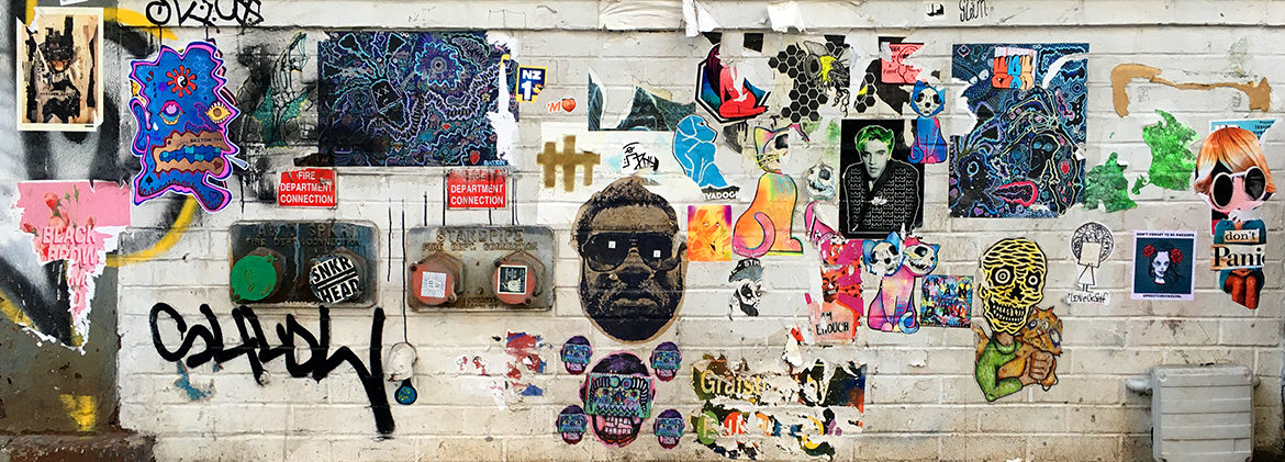 A white wall gallery filled with paste up art illustrations, paintings and stickers