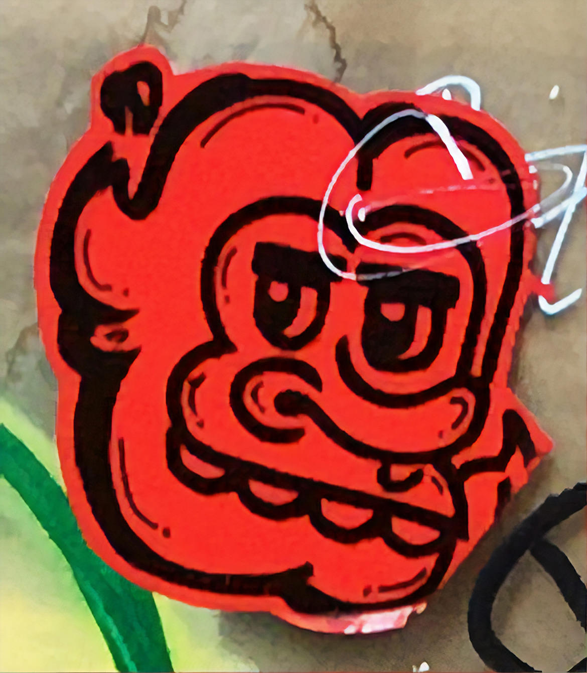 A graffiti sticker of a cartoon face in red and black